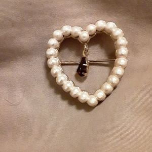 faux pearl broach w/ a red stone